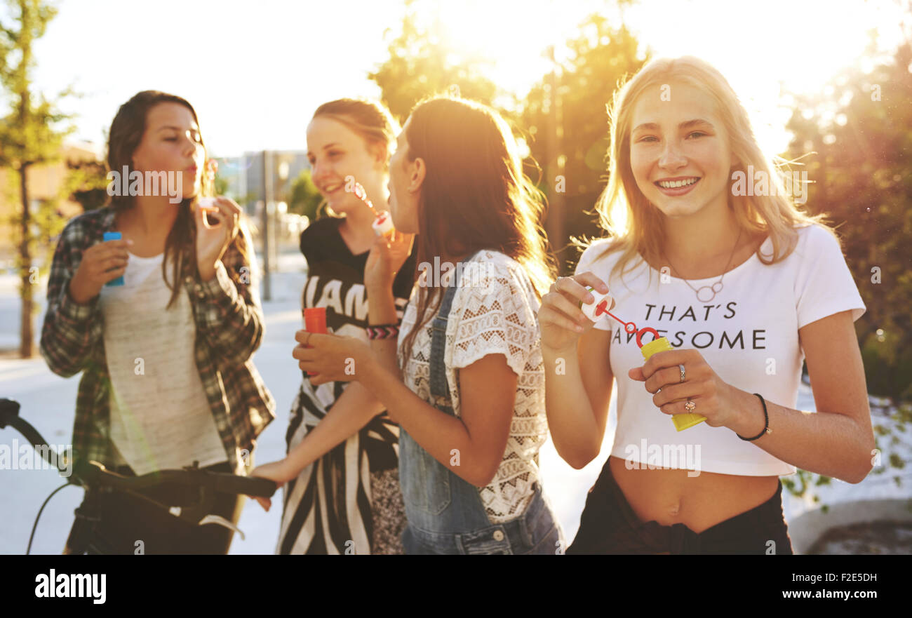 Group of friends outside hanging out and laughing - Stock Image