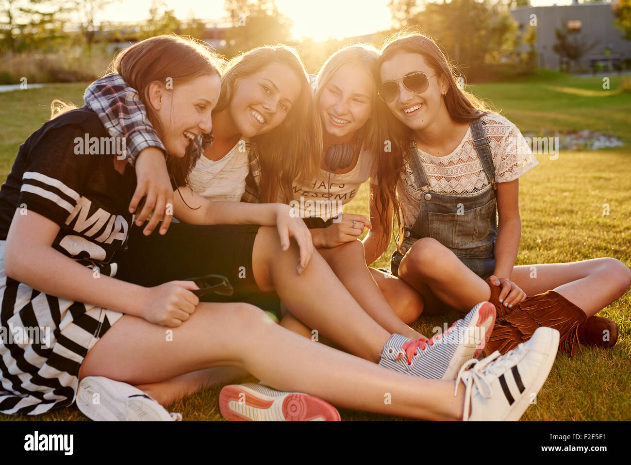 Best friends hanging out on a summer evening in a park - Stock Image
