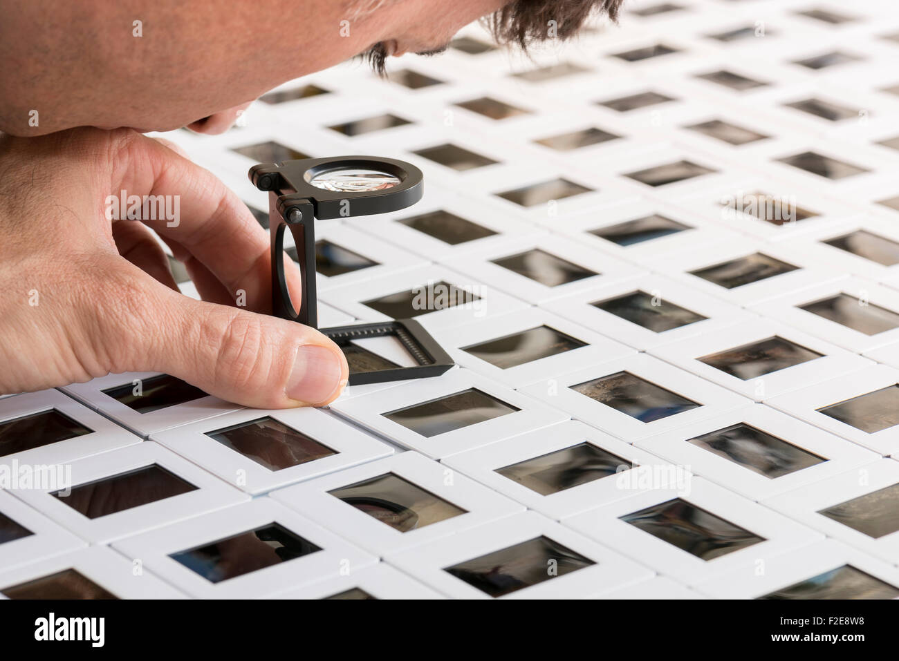 man looking through the loupe a series of slide - Stock Image