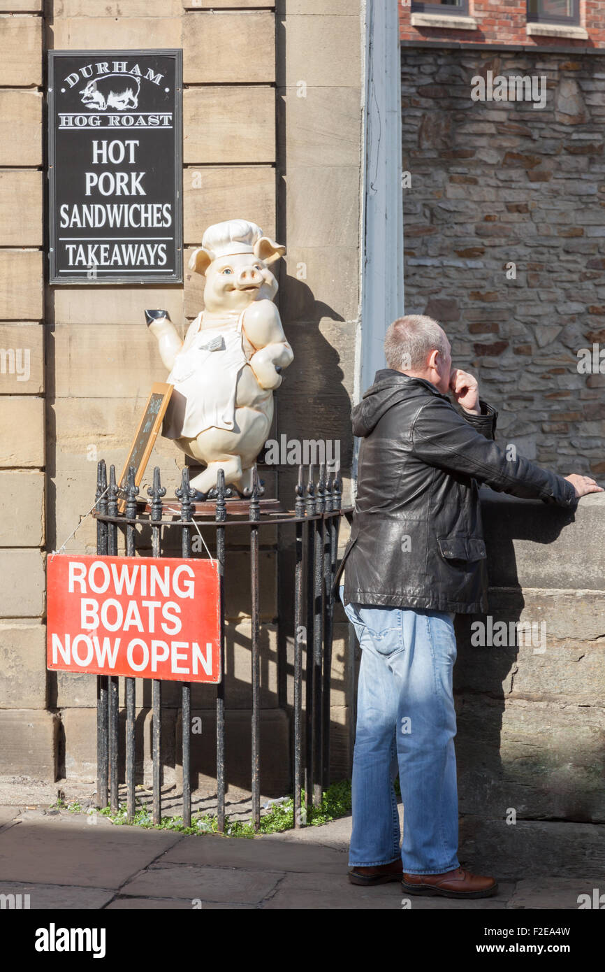 Advertising sign and pig chef model for cafe, and man looking at the River Wear from the Elvet bridge, Durham, UK Stock Photo