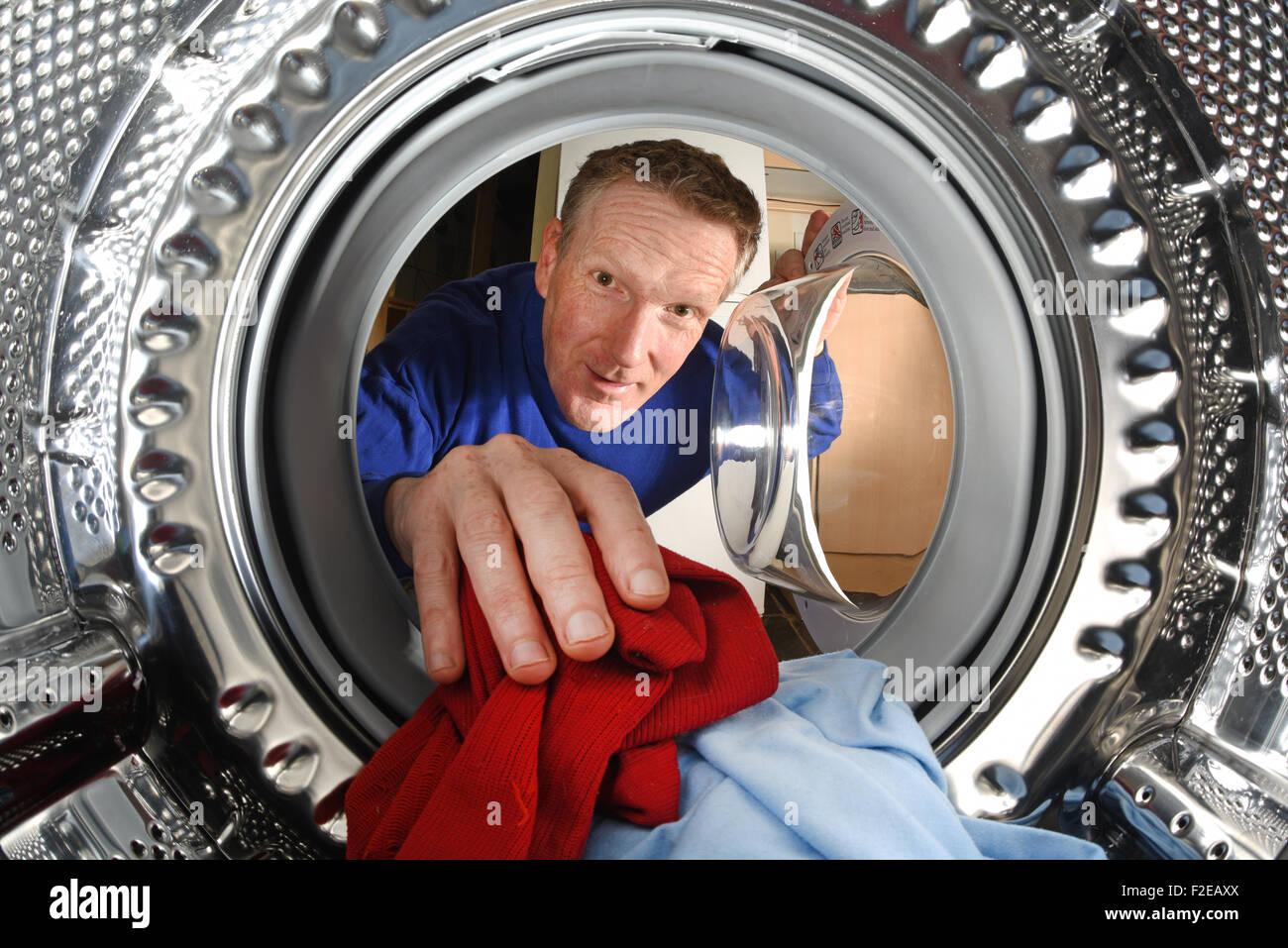 man taking washing out of washing machine - Stock Image