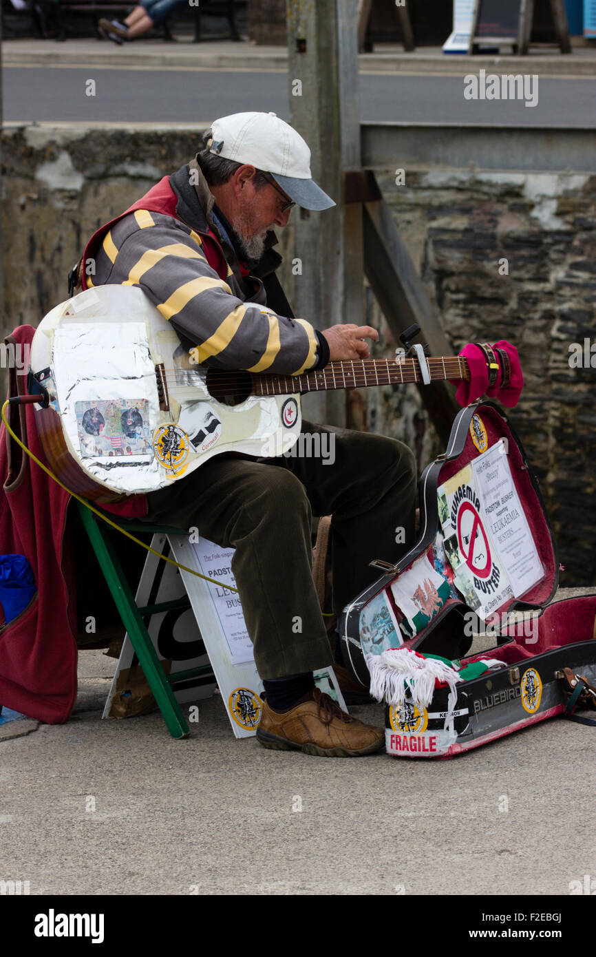 Long established charity busker playing on Padstow, Cornwall, UK outer harbour wall - Stock Image
