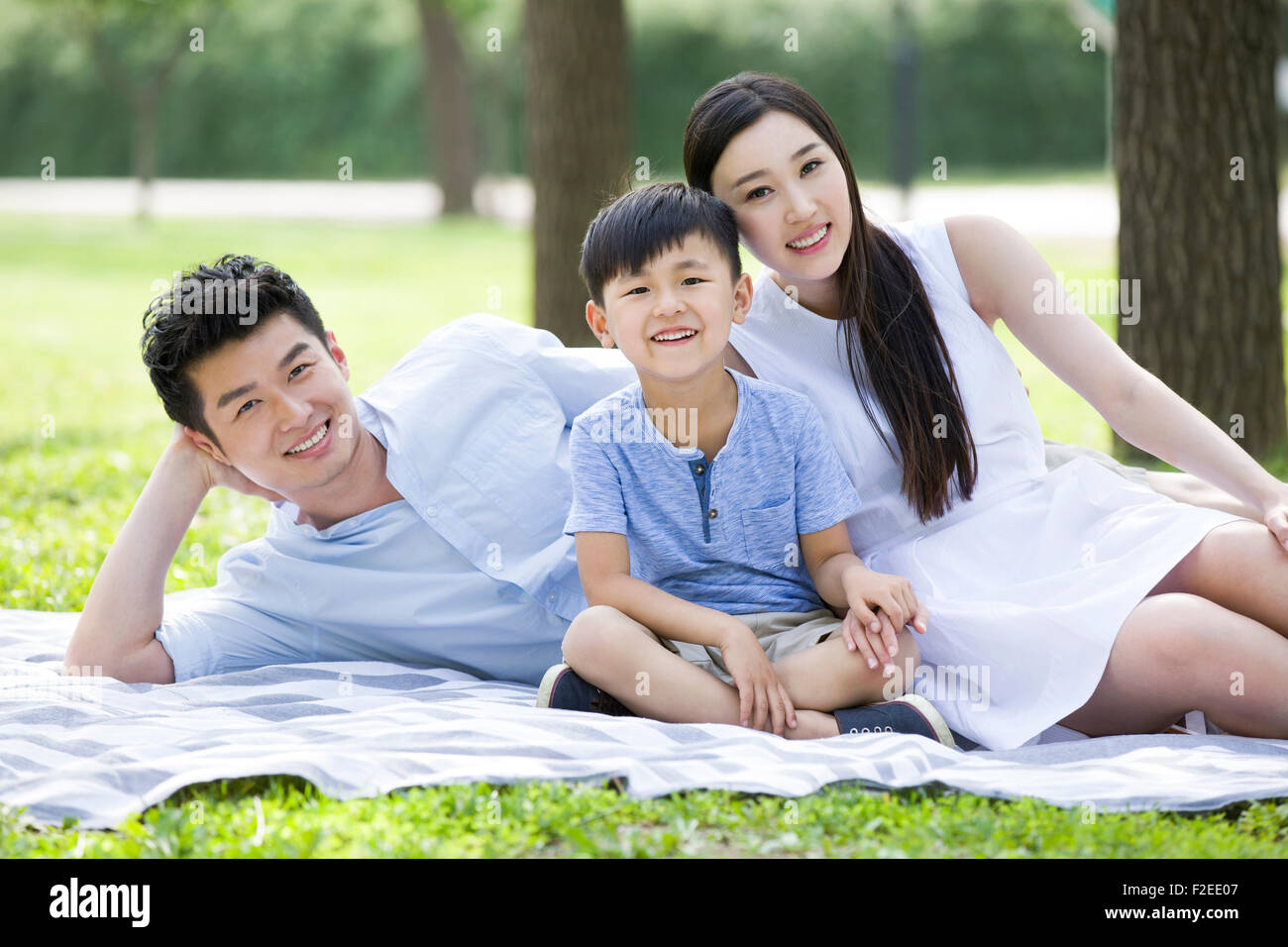 Happy young family sitting on grass - Stock Image
