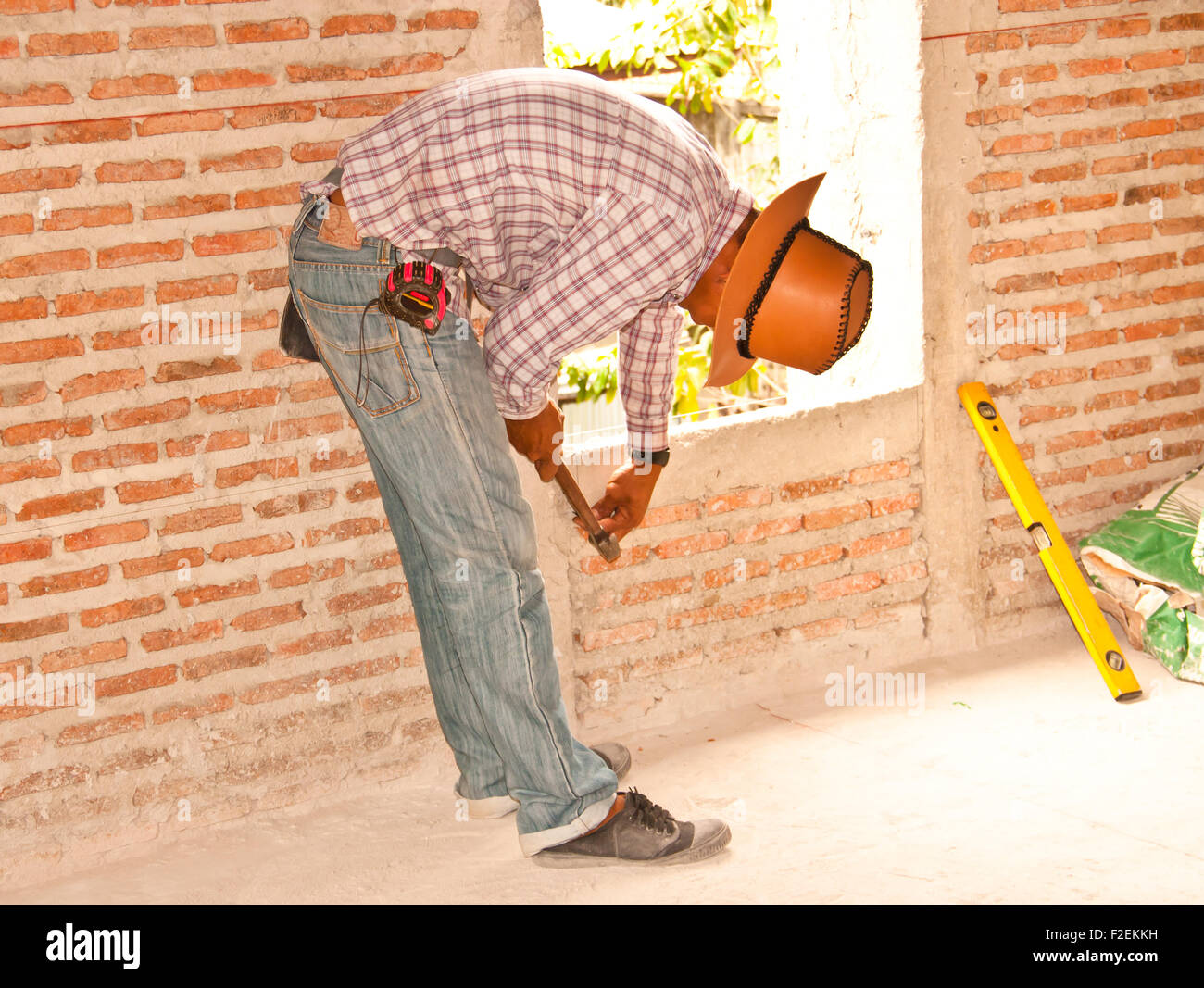 Construction workers are preparing a brick wall. - Stock Image