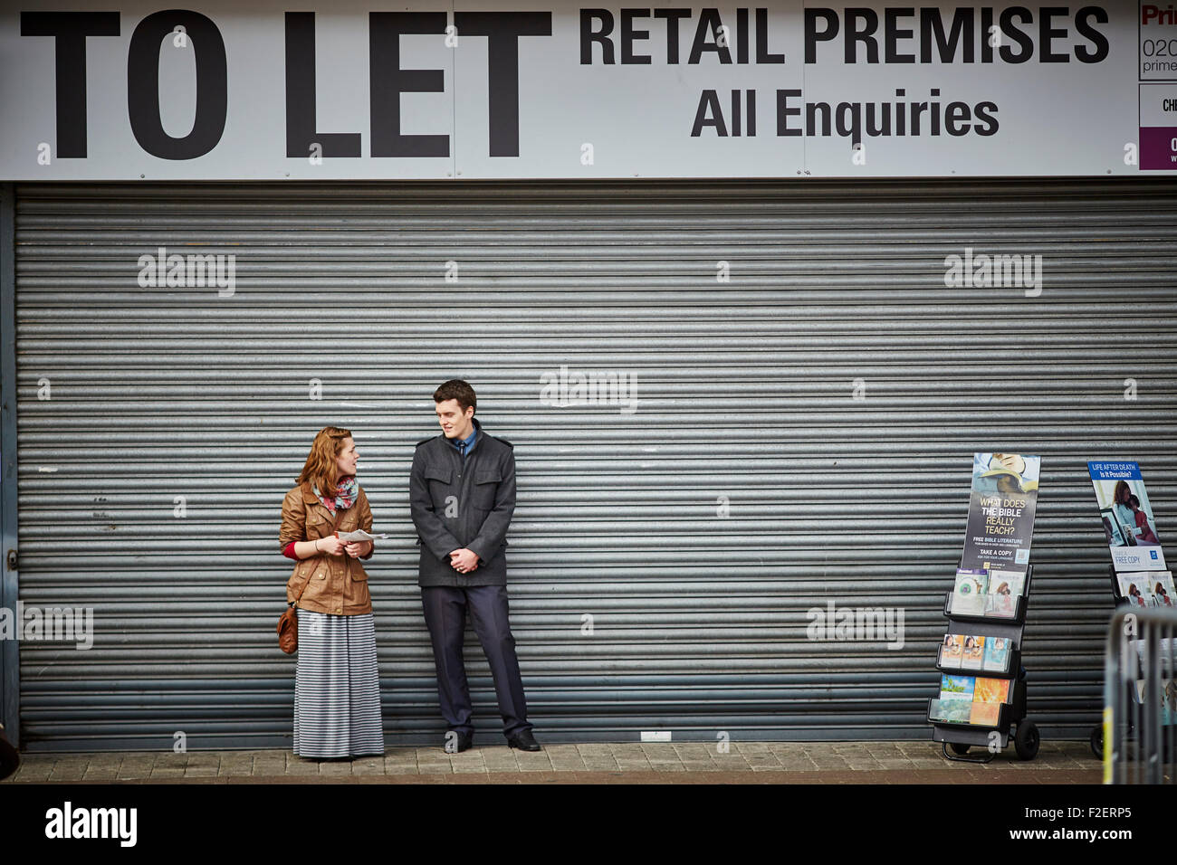 Bolton town centre to let shop space with shutters down used as a space for religious people to hand out literature - Stock Image