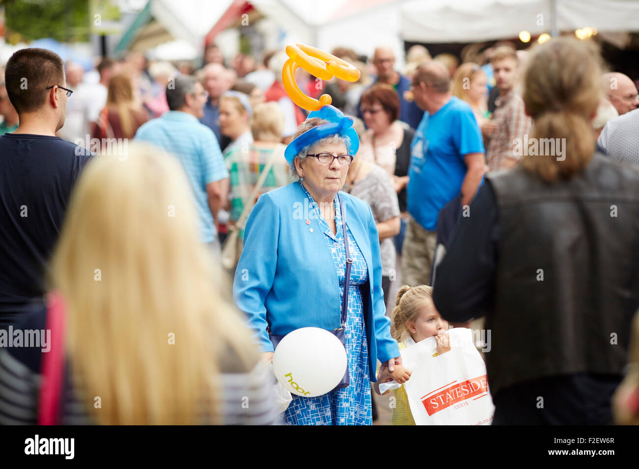 ALDI sponsored 10th Bolton Food and Drink Festival 2015  a grandma walks through the crowds with a balloon modelled - Stock Image