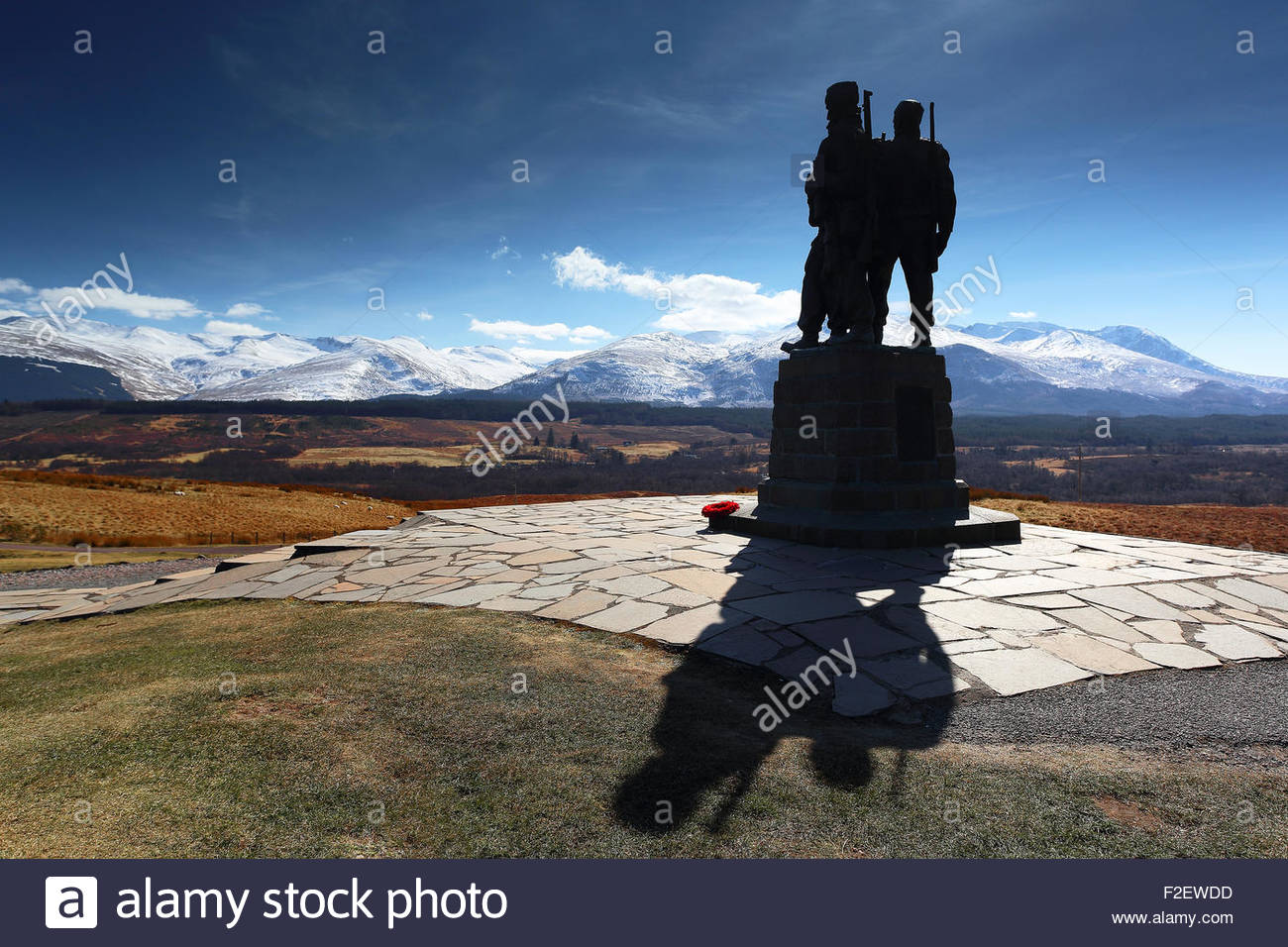 The Commando memorial monument in silhouette with the snow covered Ben Nevis mountain range in the distance. - Stock Image