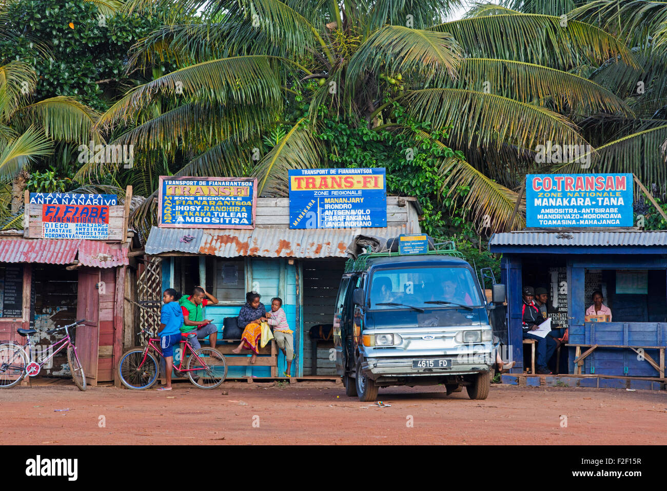Taxi-brousse minibus waiting at taxi brousse station / parcage with cooperative booths of different agents, Manakara, - Stock Image