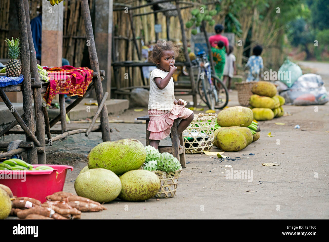 Malagasy girl at roadside market stall selling durian, jackfruit , vegetables in rural village, Vatovavy-Fitovinany, - Stock Image