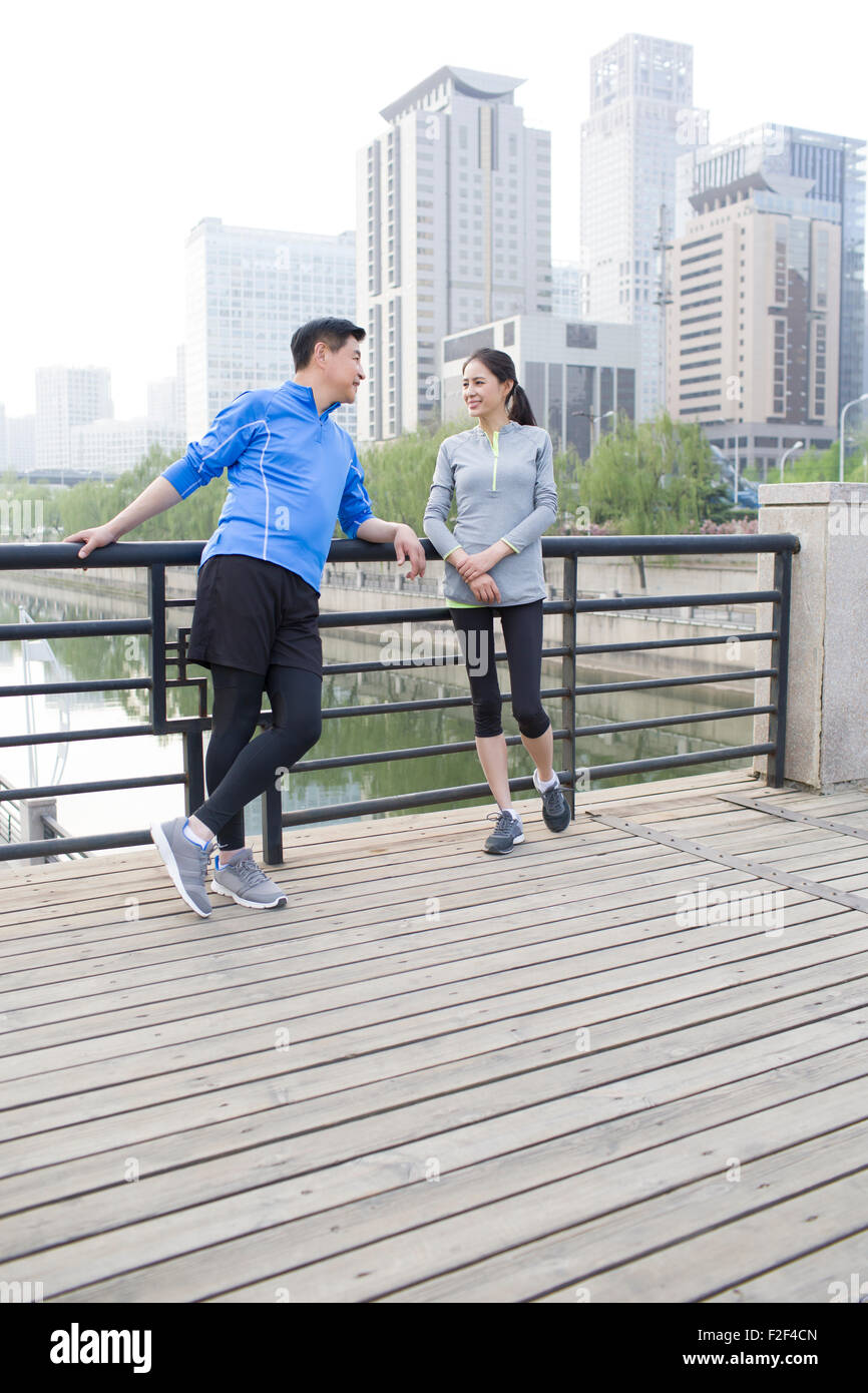 Happy mature couple resting after exercising - Stock Image