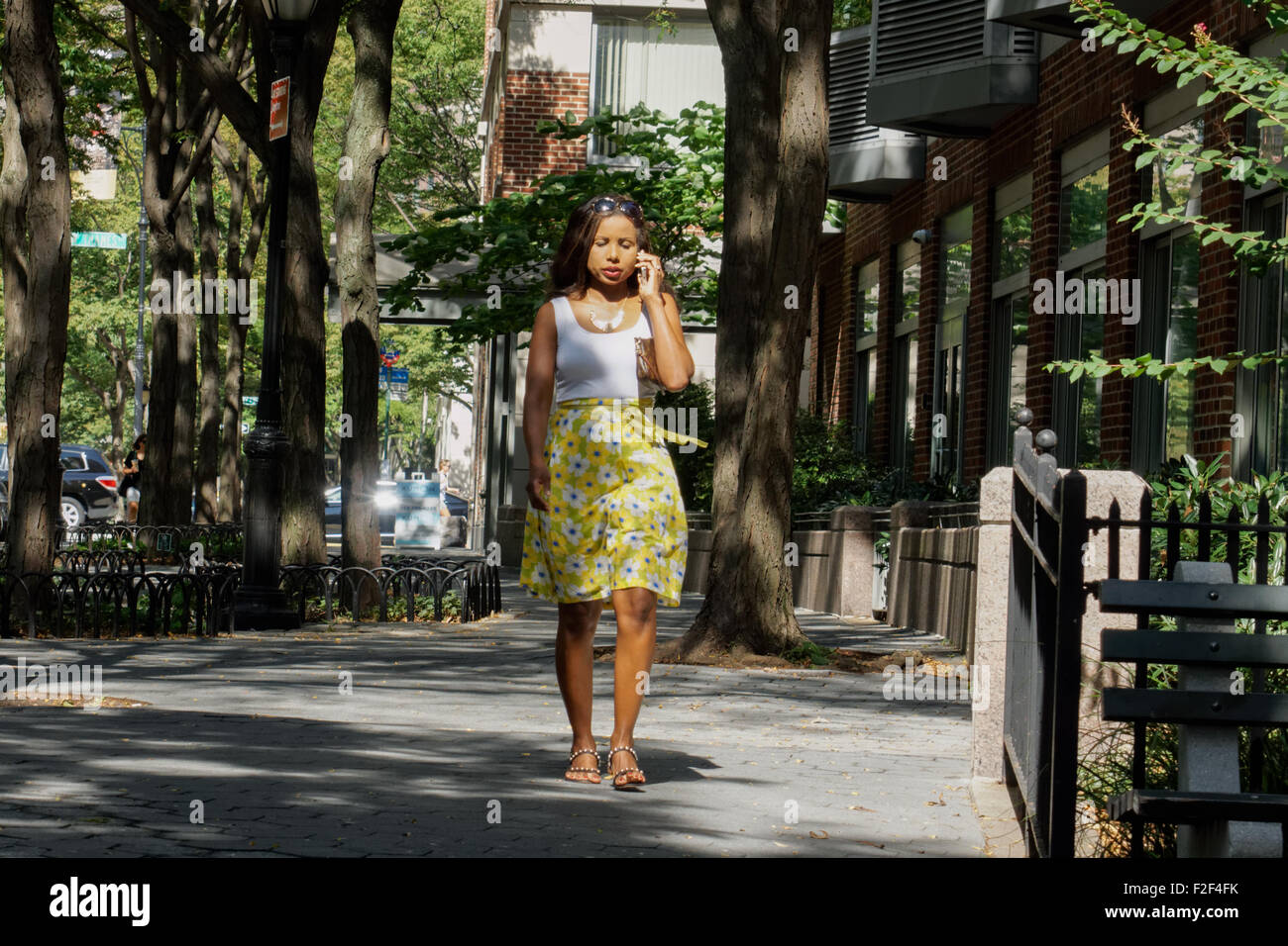 A young woman talking on a cellphone in Battery Park City, a neighborhood in Manhattan, New York City. - Stock Image
