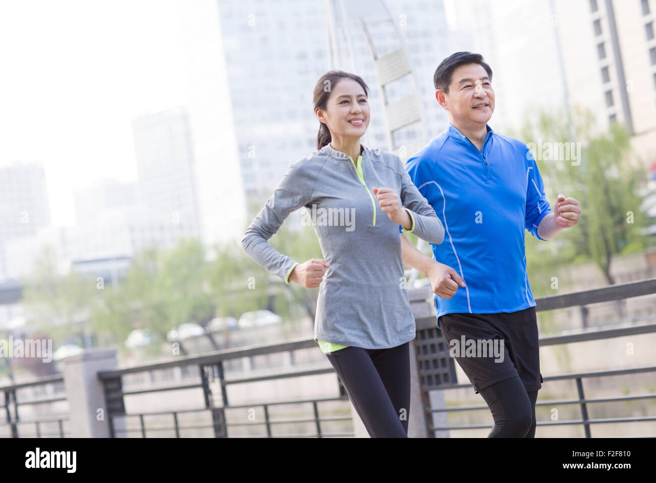 Happy mature couple running in park - Stock Image