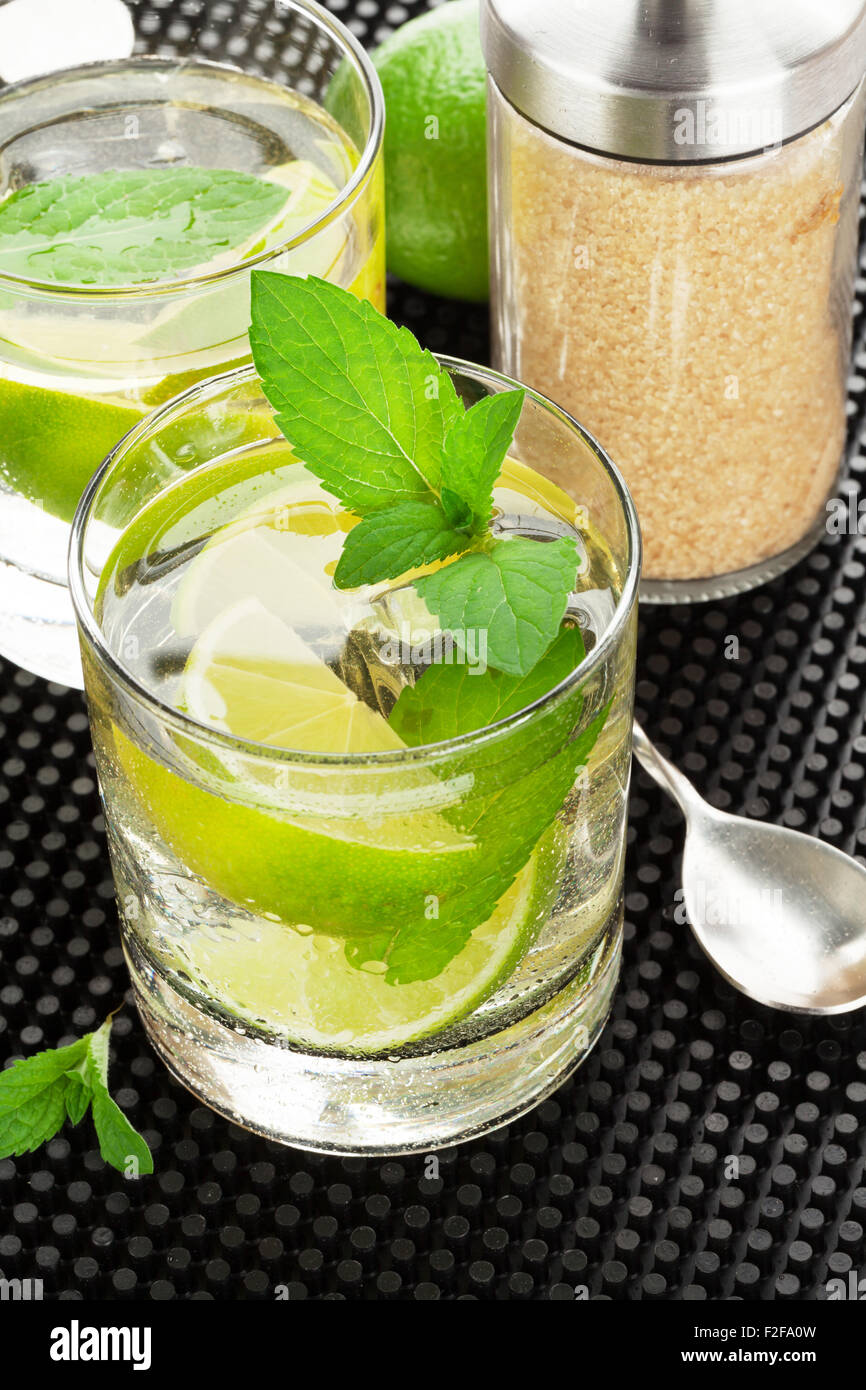 Mojito cocktail and ingredients on black rubber mat - Stock Image