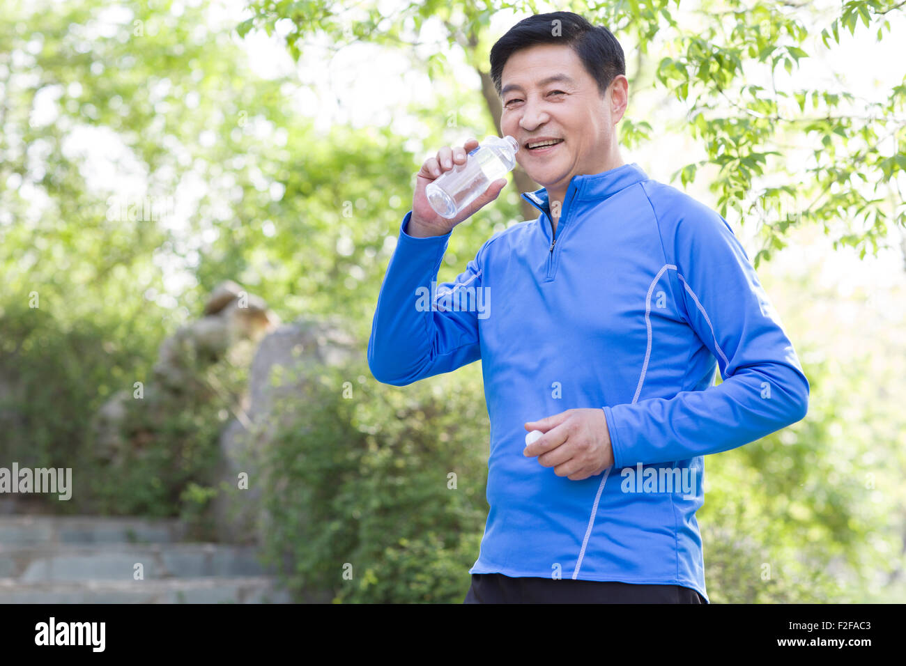 Happy mature man drinking water after exercising - Stock Image
