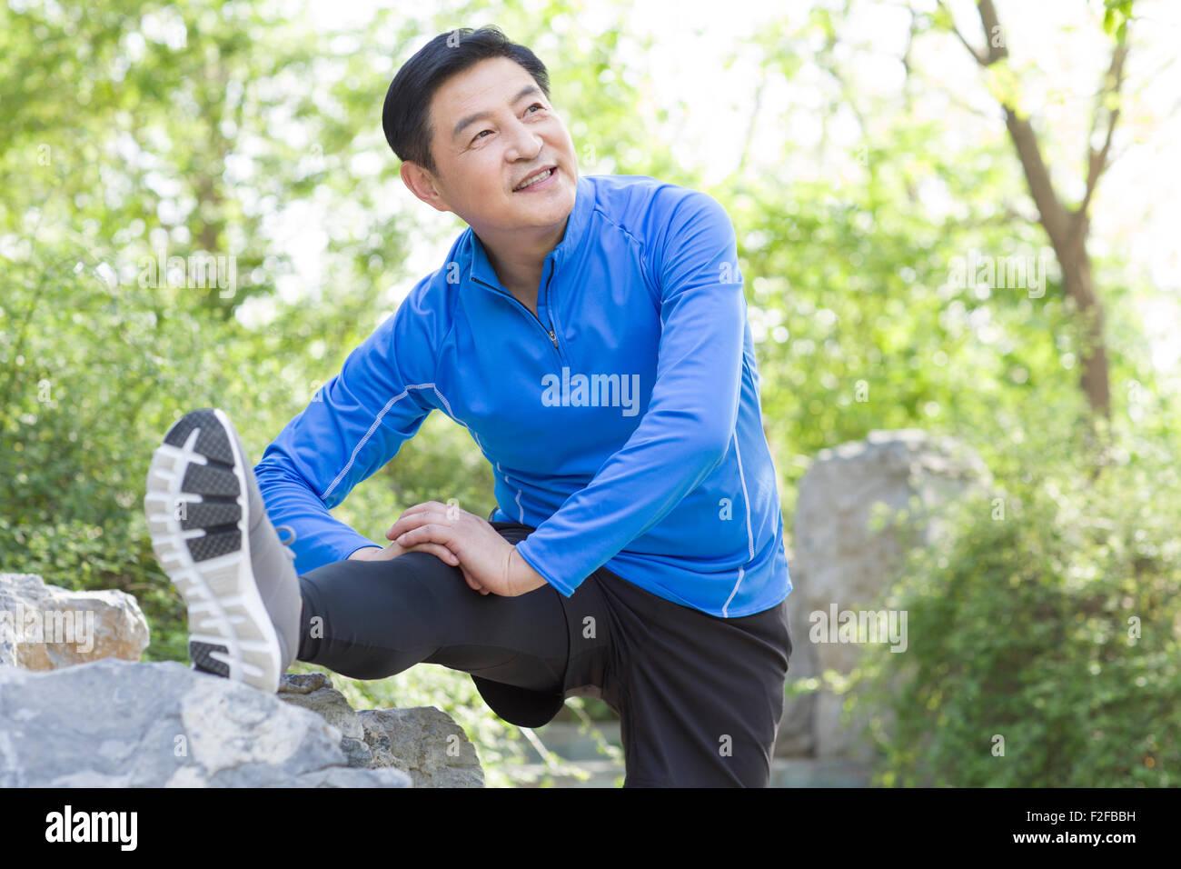Happy mature man exercising in park - Stock Image