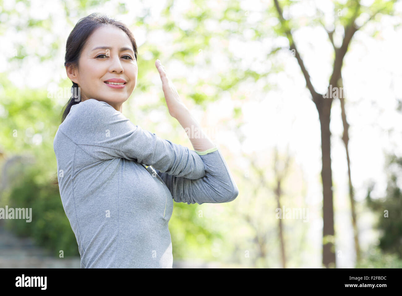 Happy mature woman exercising in park - Stock Image