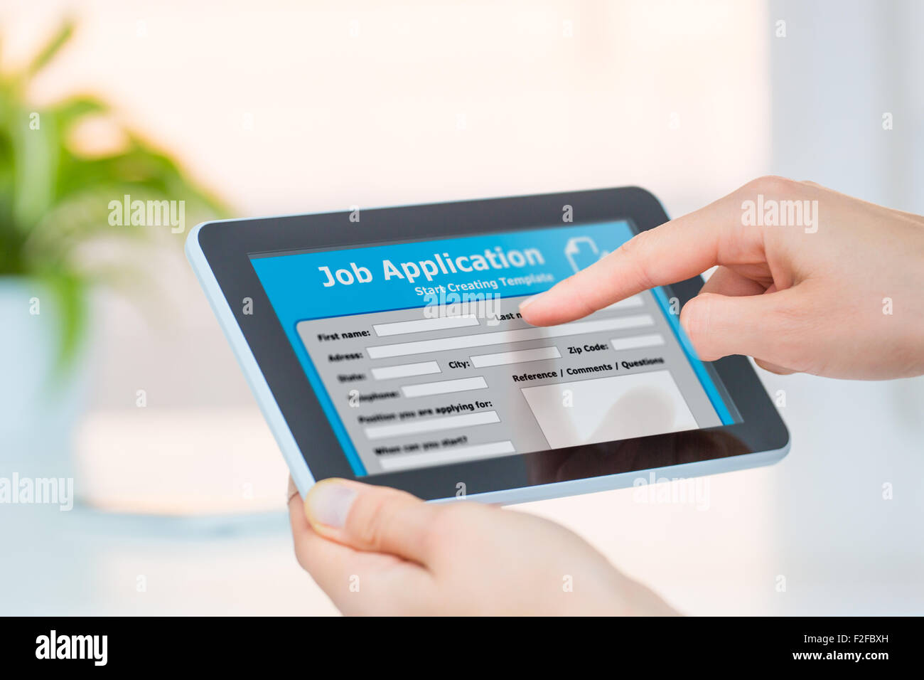 Applicant filling up the online job application by digital tablet. - Stock Image