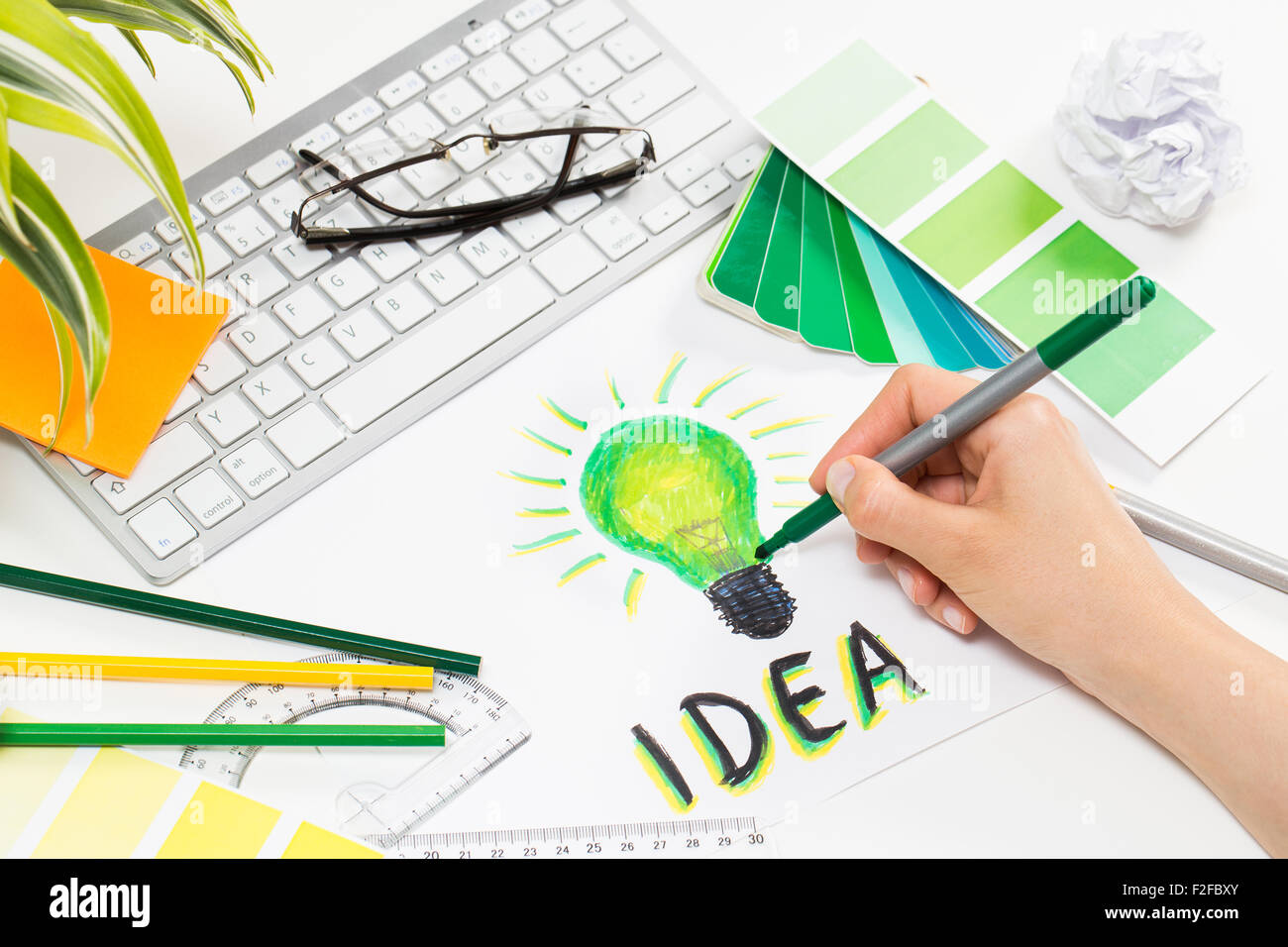 Designer drawing a green light bulb. Brainstorming and inspiration cocnept. - Stock Image