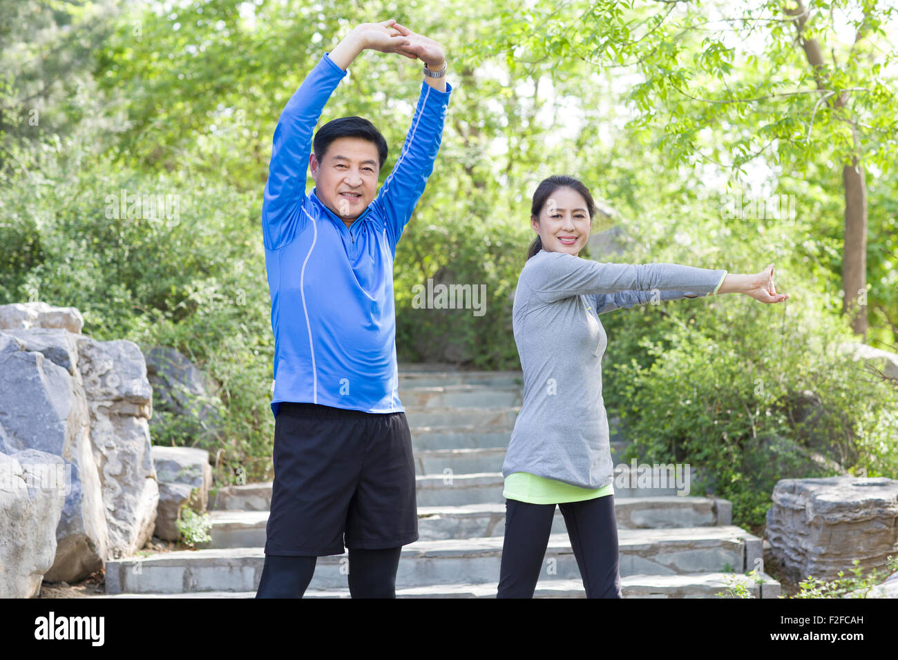 Happy mature couple exercising in park - Stock Image