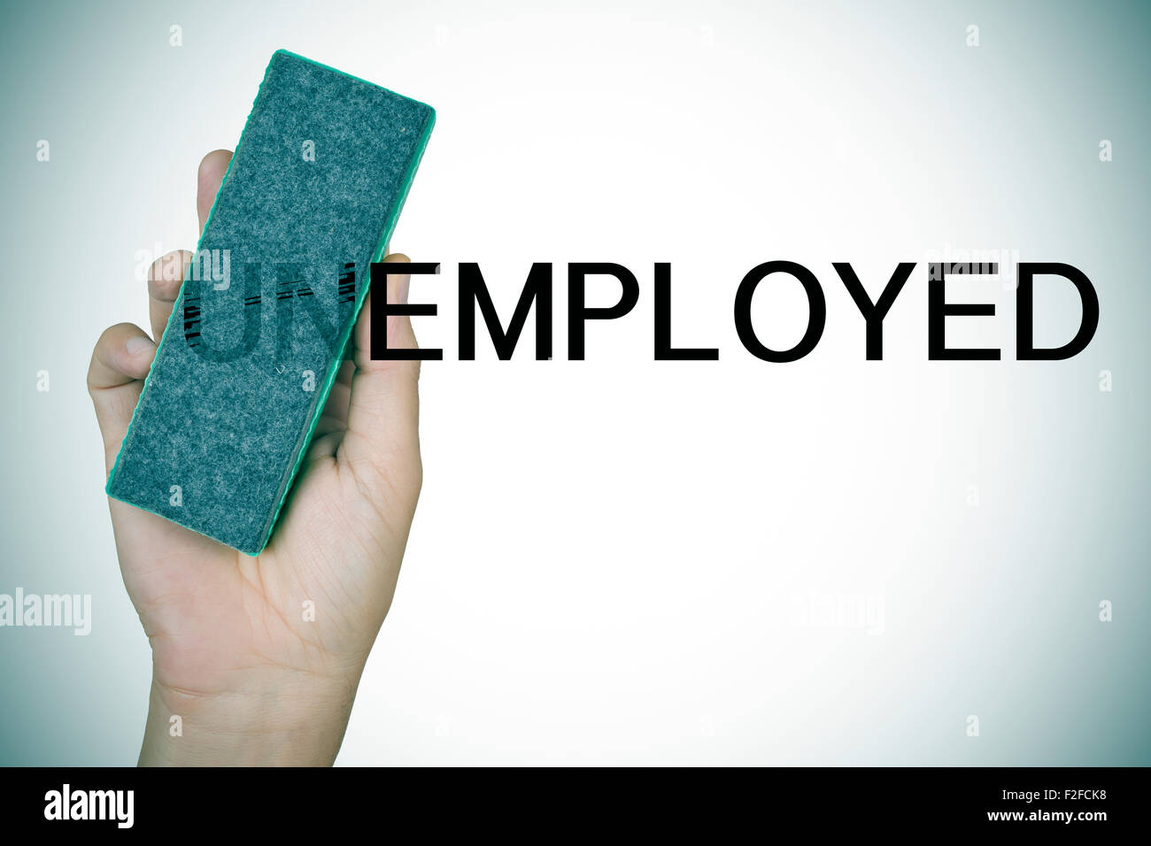 closeup of the hand of a young man deleting the prefix UN in the word unemployed with an eraser to convert it in - Stock Image