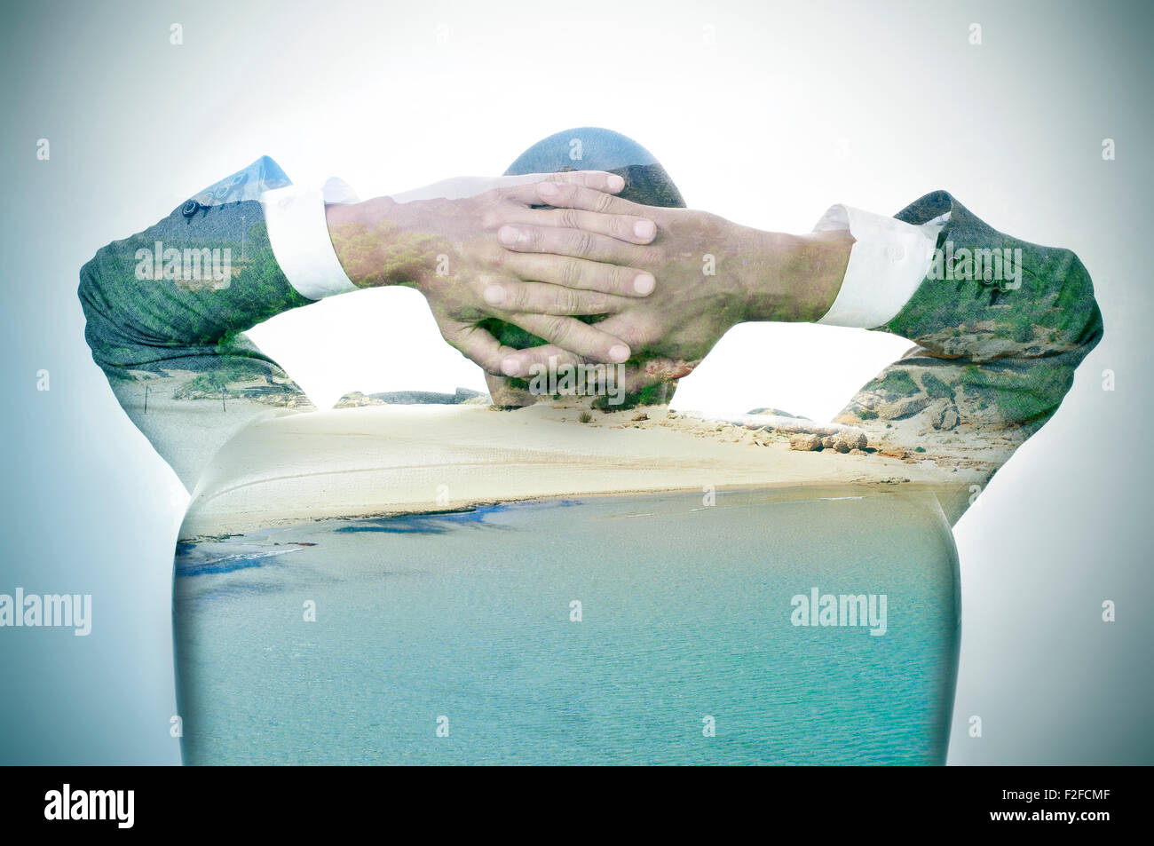 double exposure of a young businessman seen from behind relaxing in his office chair and a relaxing beach - Stock Image