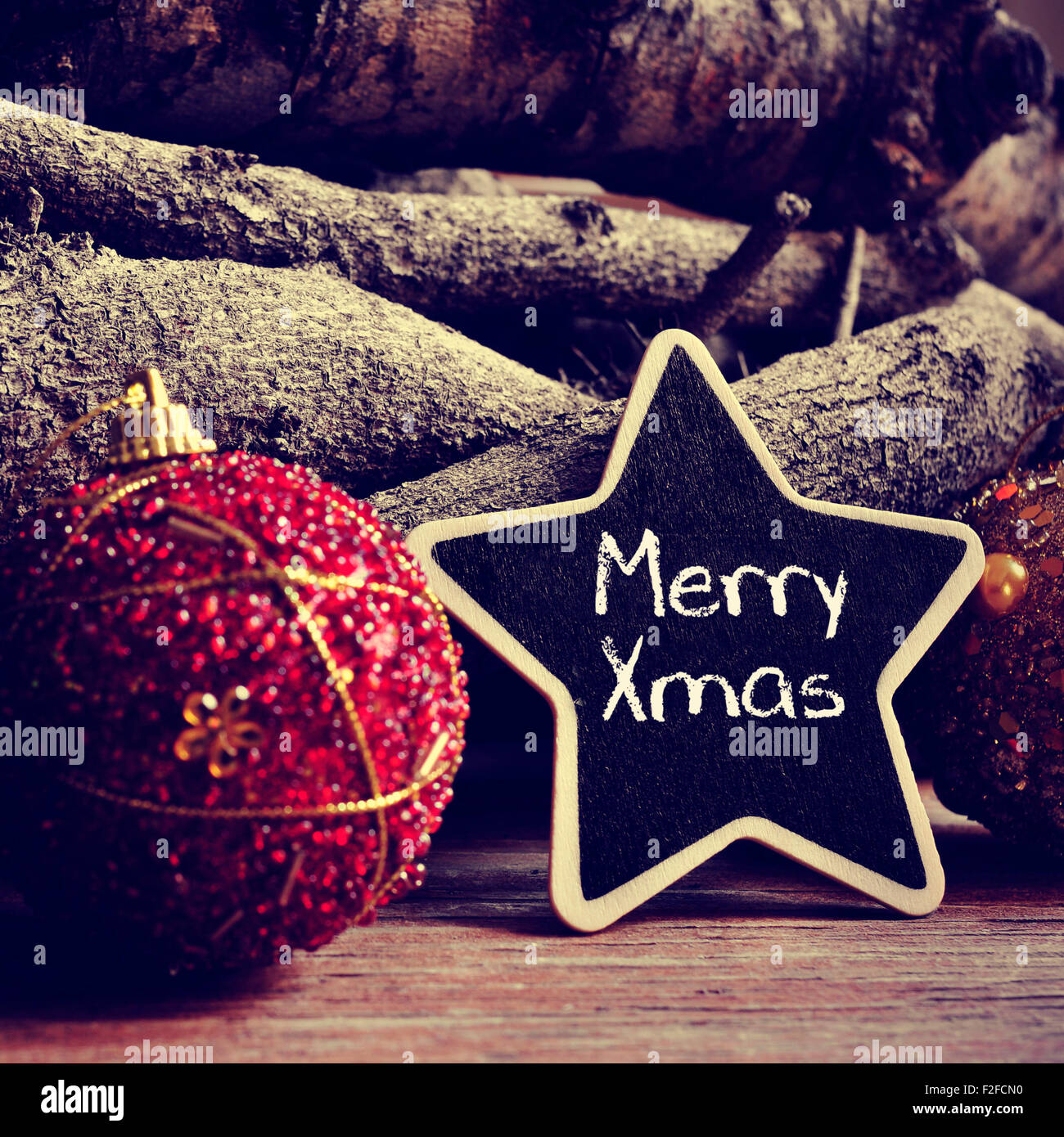 the text merry xmas written in a star-shaped blackboard, and some christmas ornaments, and pinecones and a pile - Stock Image