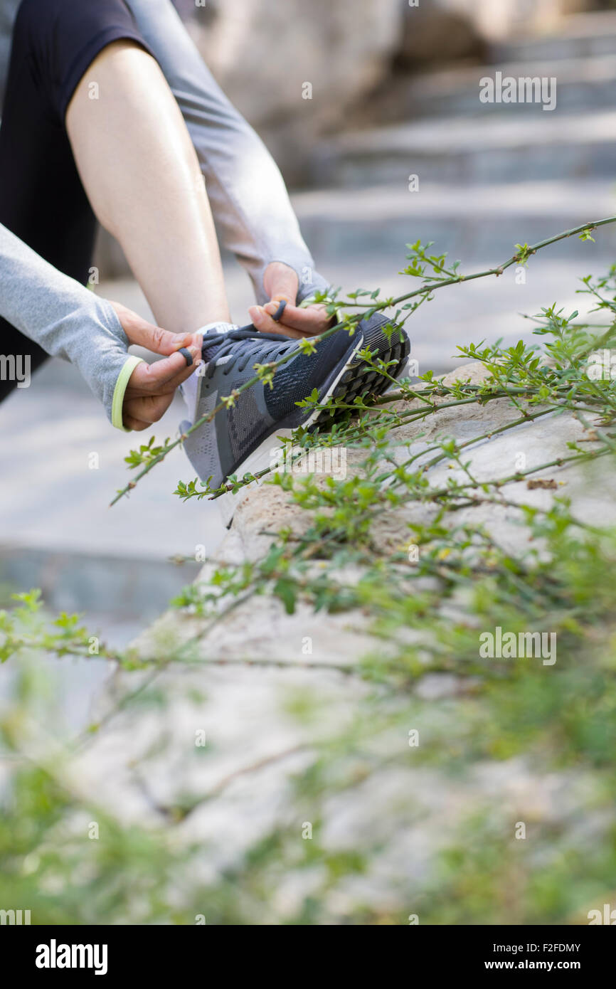 Mature woman tying her shoelaces - Stock Image