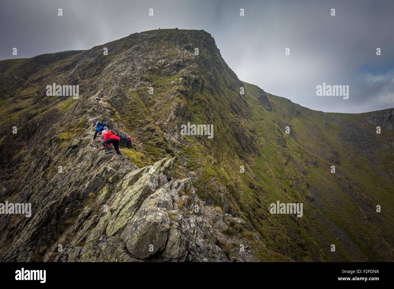 Men socialising - People scrambling up Sharp Edge, a Grade 1 scramble to reach the summit of Blencathra mountain Stock Photo