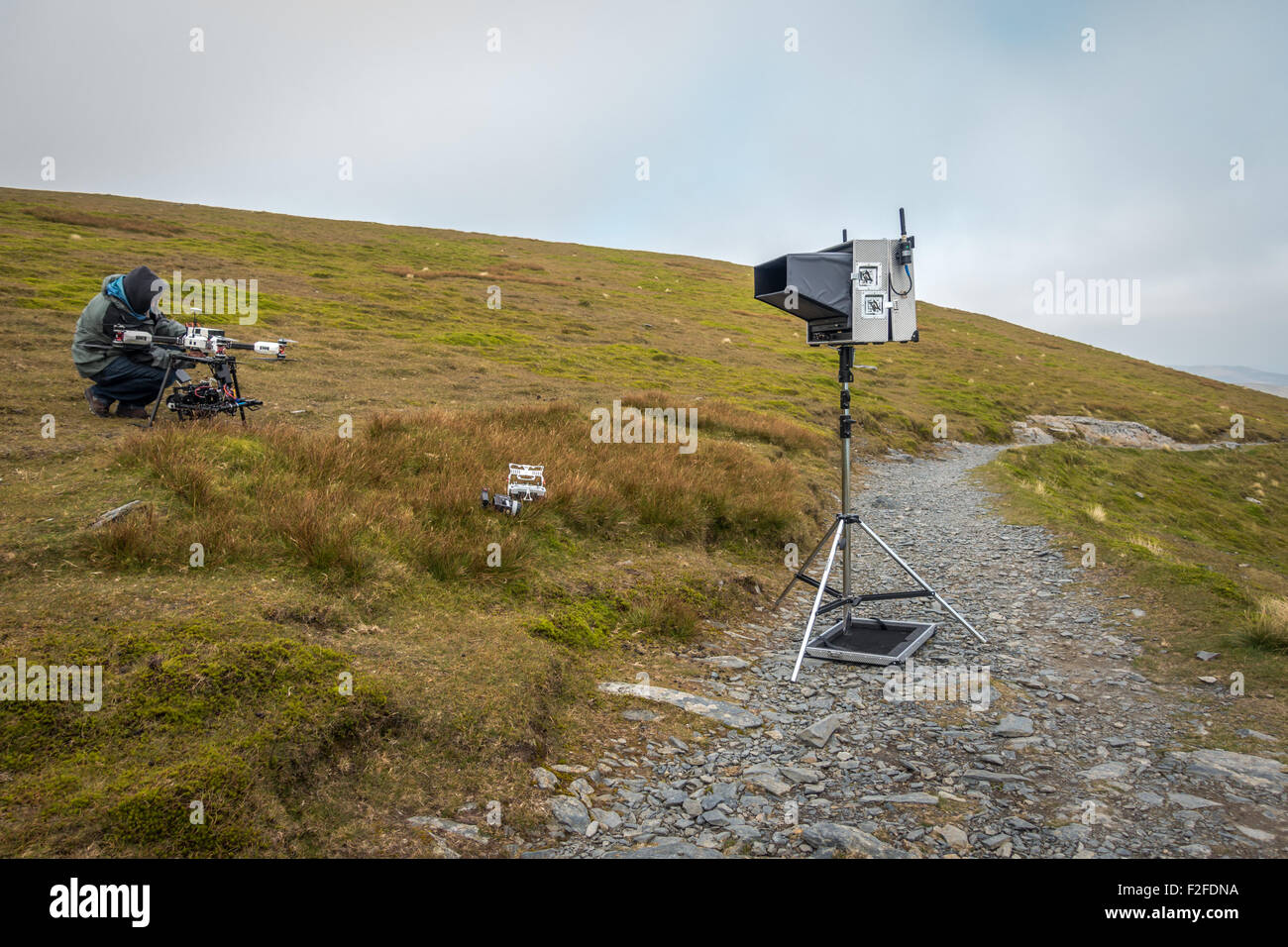Film crew preparing a large expensive filming drone on the top of a mountain in the Lake District (Blencathra) - Stock Image