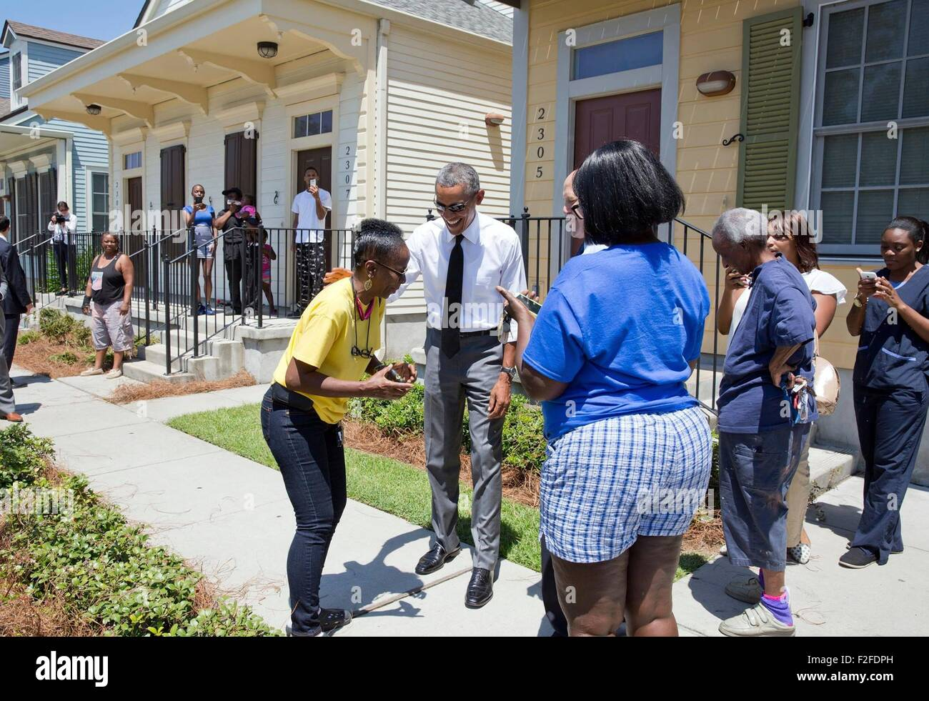 U.S. President Barack Obama jokes with residents in front of their homes during a walk through the Treme neighborhood - Stock Image