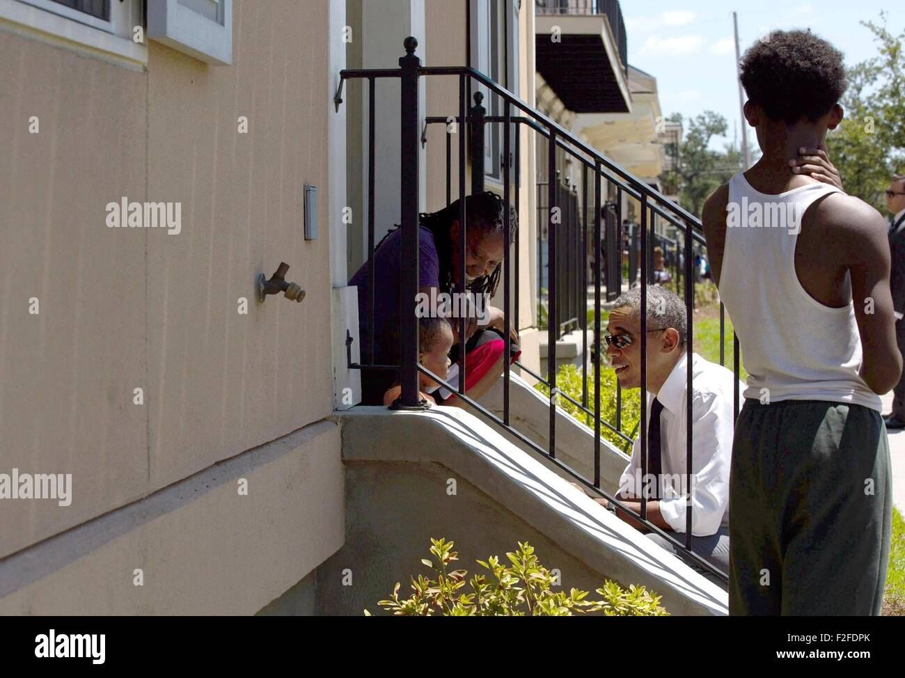 U.S. President Barack Obama speaks with residents in front of their homes during a walk through the Treme neighborhood - Stock Image