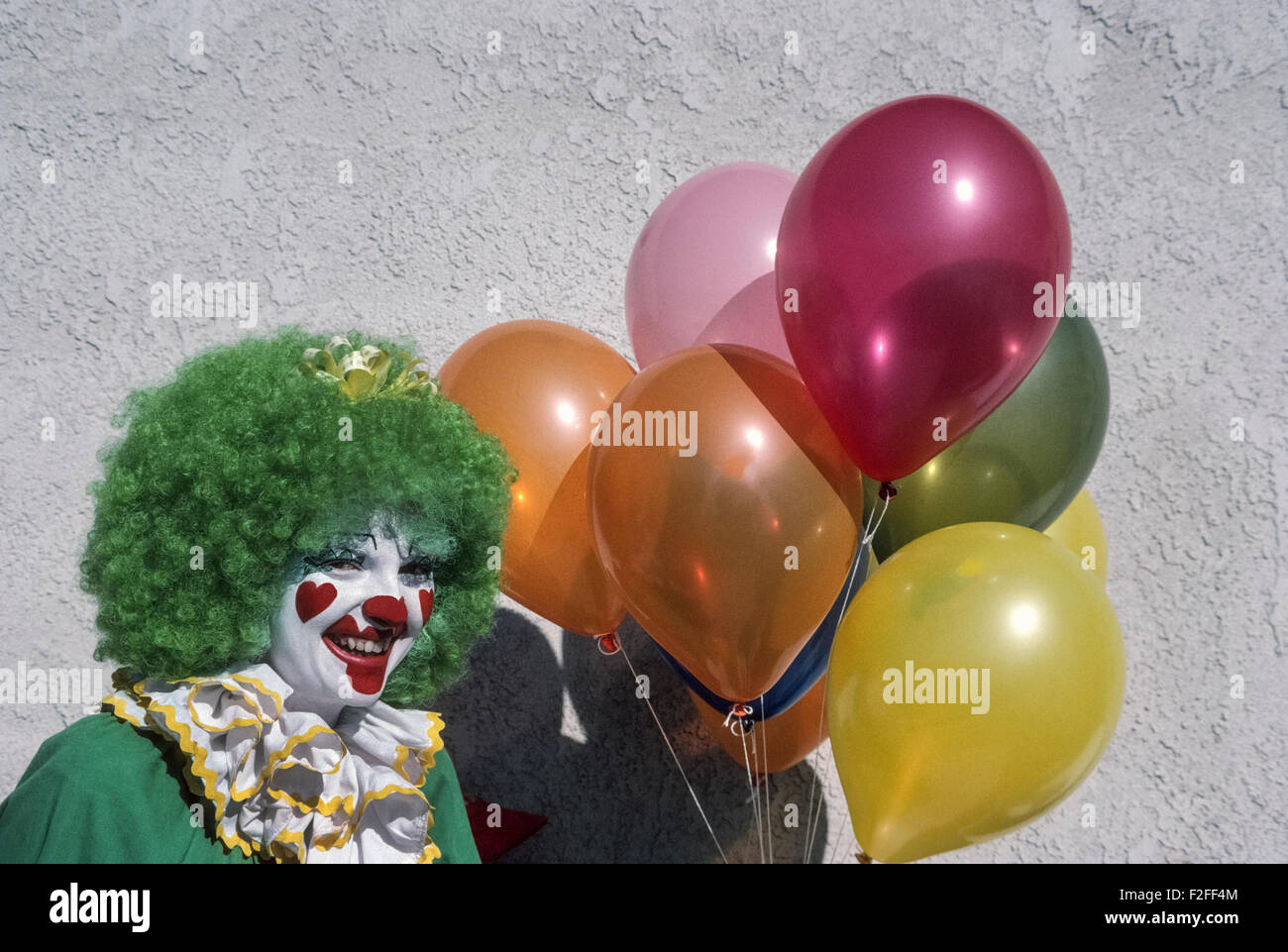 A costumed circus clown with curly green hair and a smiling painted face stands by a gray stucco wall with a bunch - Stock Image