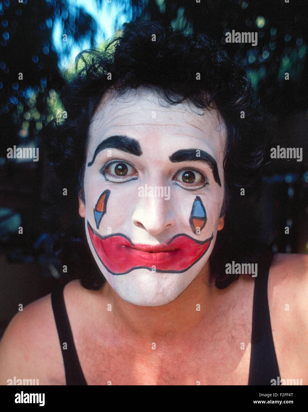 A male mime with a smile of large red lips painted on his clown face stares with big brown eyes at the camera for - Stock Image