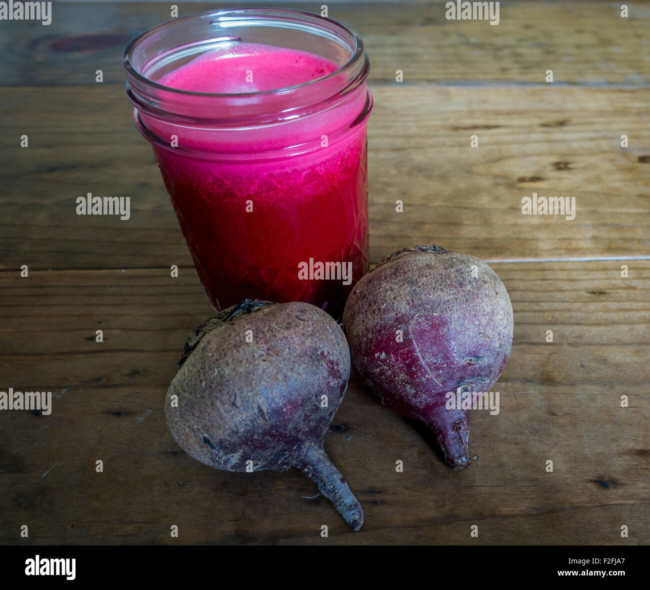 Fresh beet juice in mason jar with whole beets. Stock Photo