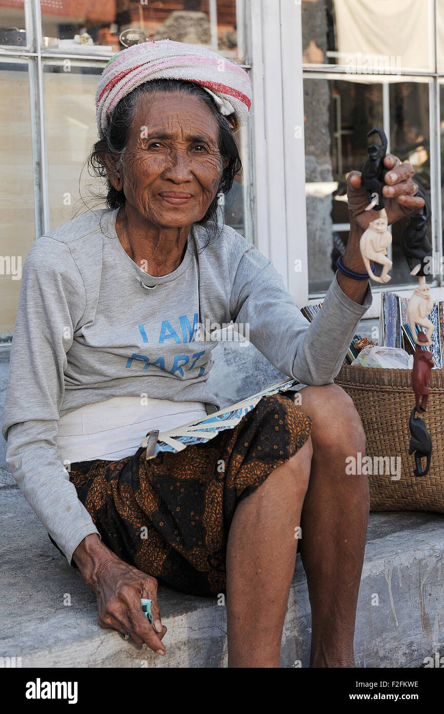 Local woman sell statues of monkeys souvenir in the Monkey forest street, Ubud, Bali - Stock Image