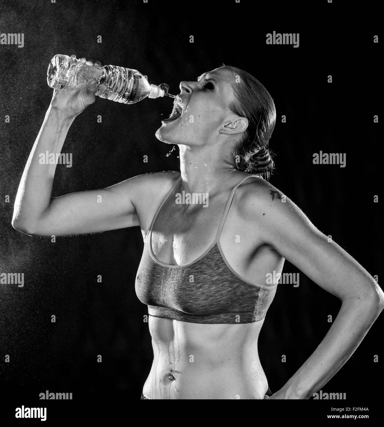 Monochrome of an Athletic Woman Drinking Water - Stock Image