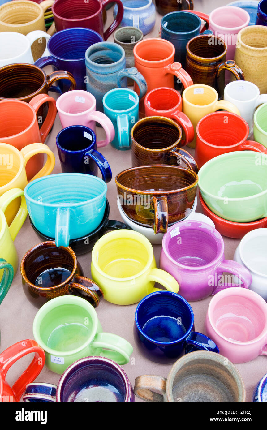Colorful mugs on sale at a farmers and craft market - Stock Image