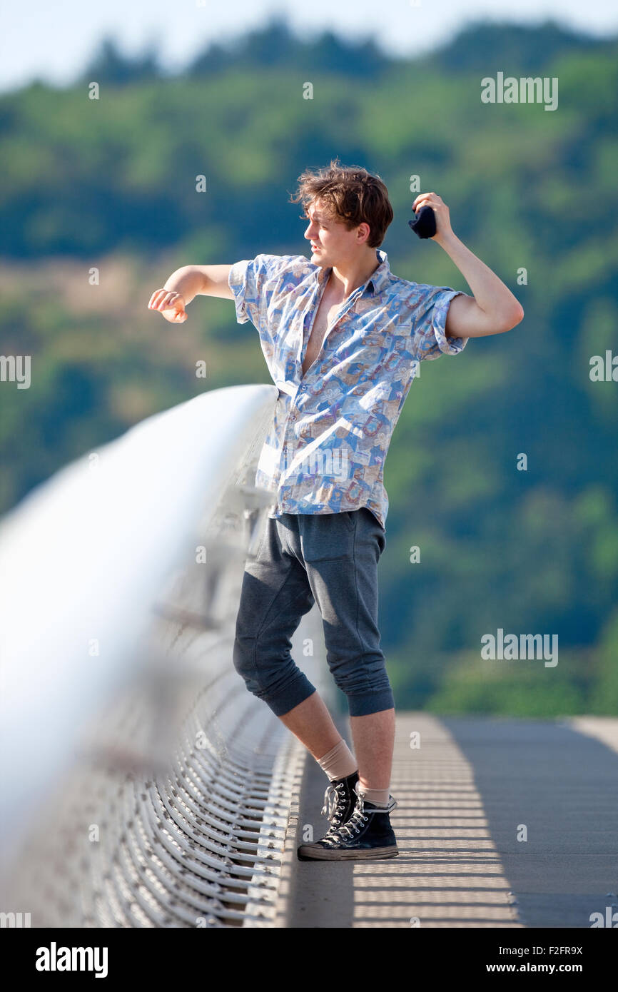 Young Man Standing on the Bridge Throwing Down Something - Stock Image