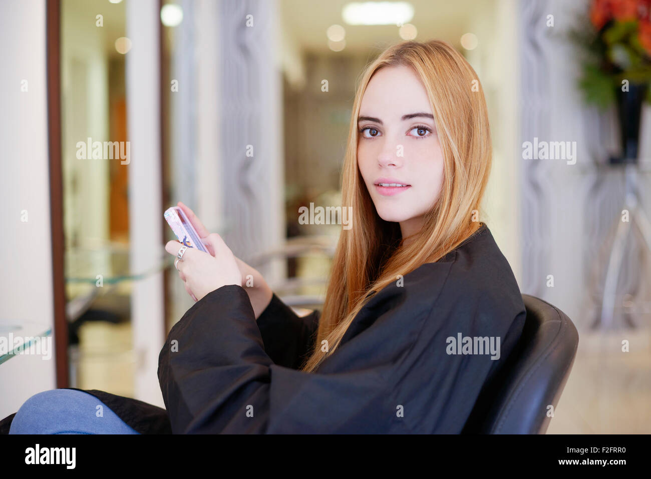 Portrait woman texting with cell phone in hair salon Stock Photo