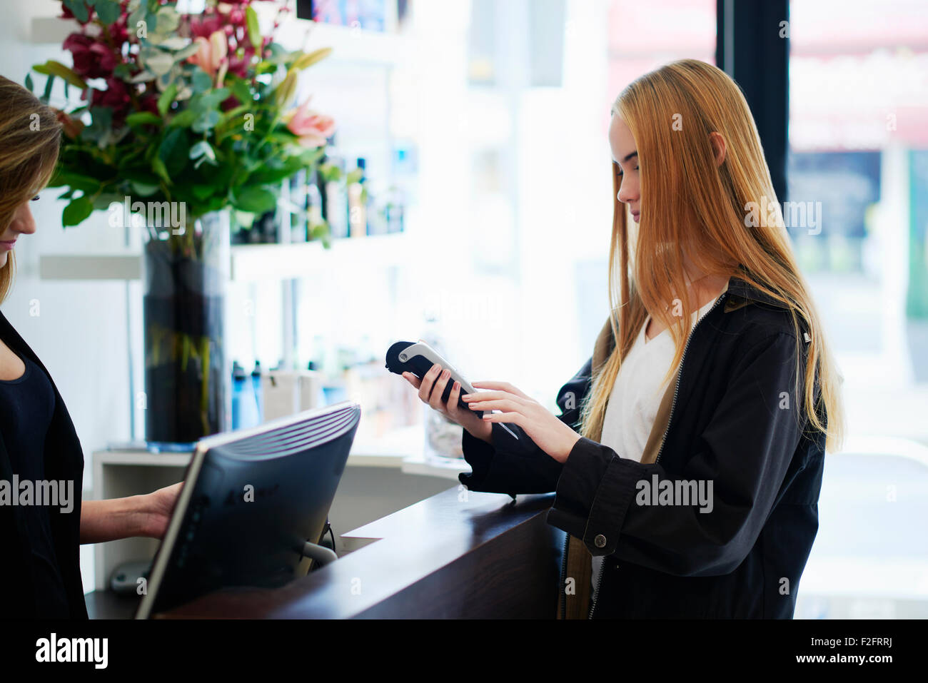 Woman paying with credit card reader at counter in hair salon Stock Photo