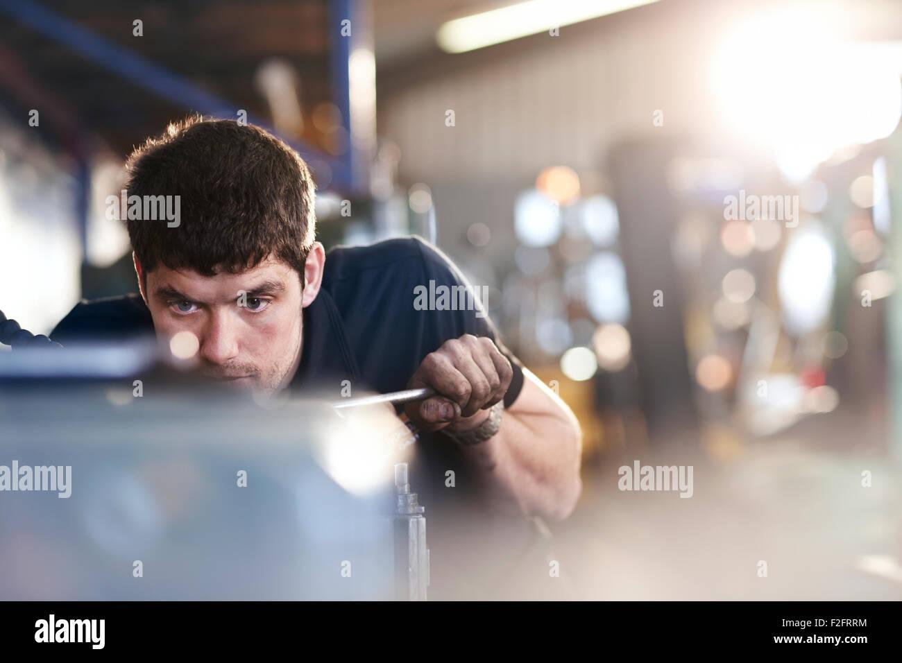 Mechanic working in auto repair shop - Stock Image