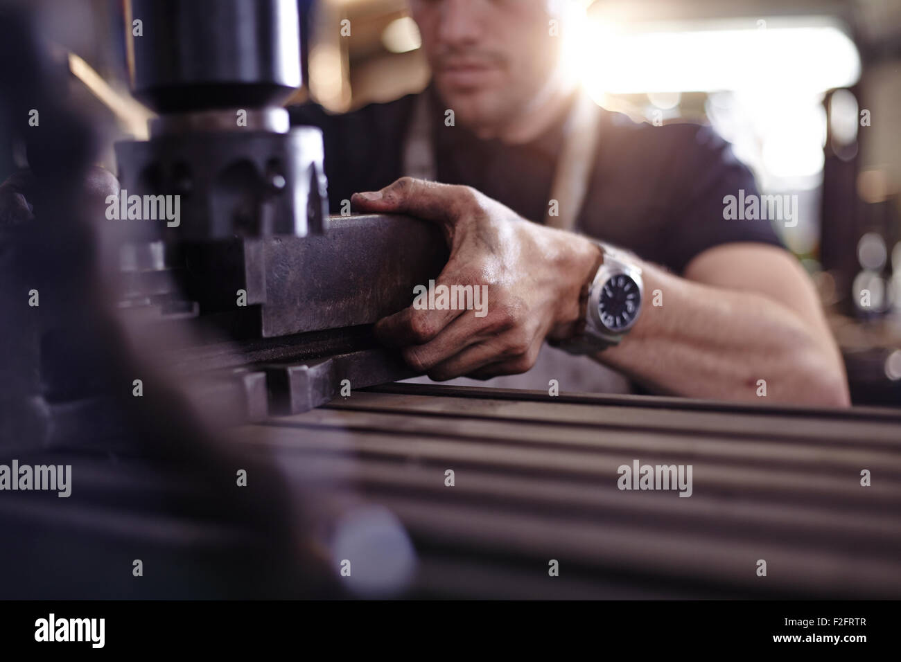 Close up mechanic using machinery in auto repair shop - Stock Image