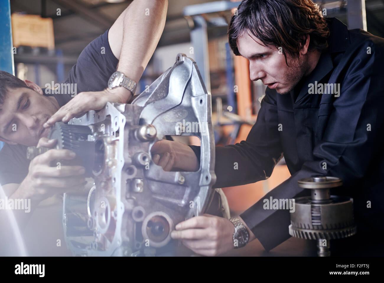 Mechanics fixing part in auto repair shop - Stock Image