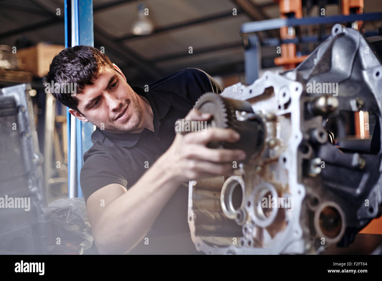 Mechanic fixing part in auto repair shop - Stock Image