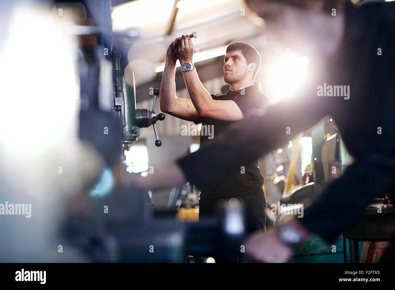 Mechanic examining part in auto repair shop Stock Photo