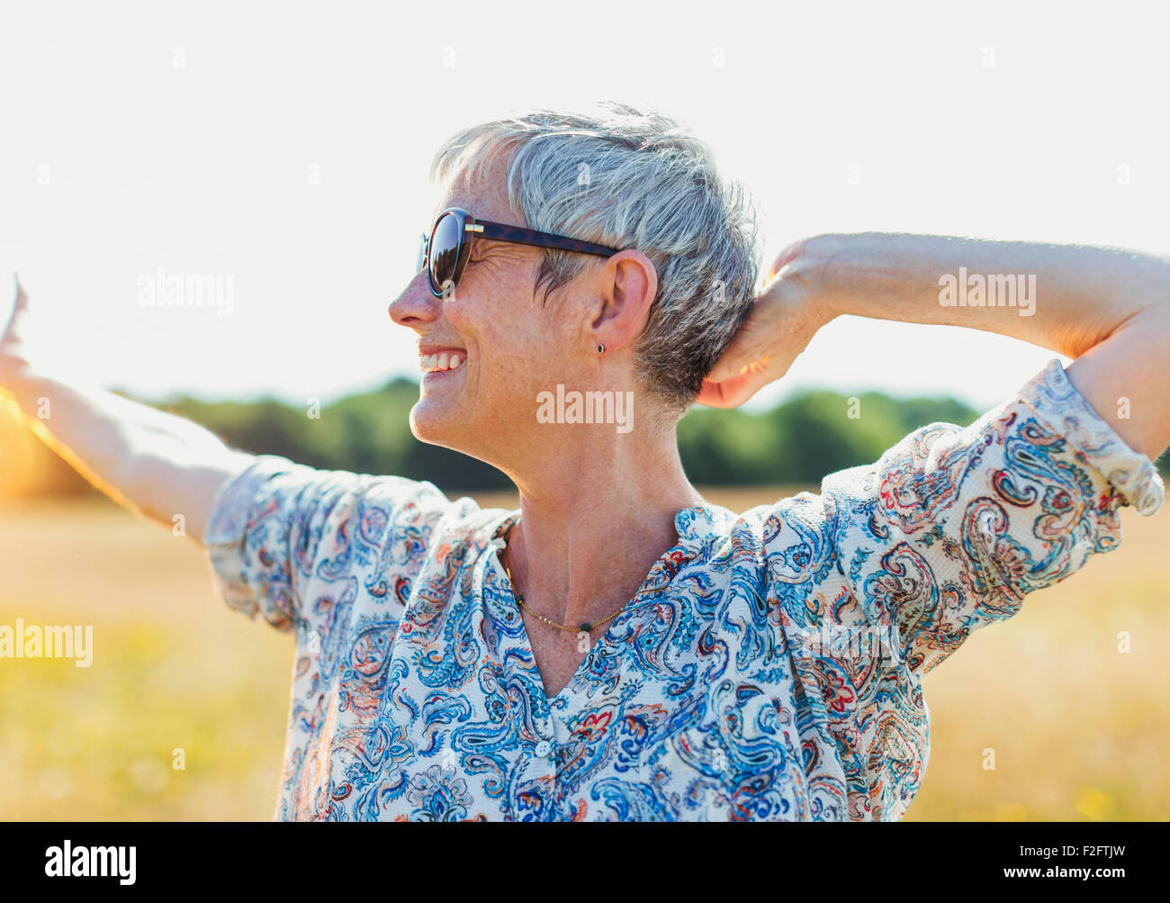 Enthusiastic senior woman with arms outstretched in sunny field - Stock Image