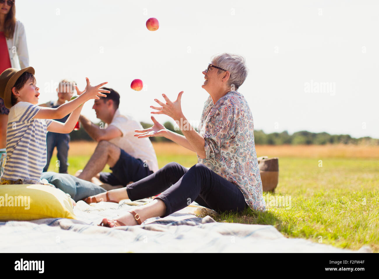 Grandmother and grandson juggling apples on picnic blanket in sunny field - Stock Image