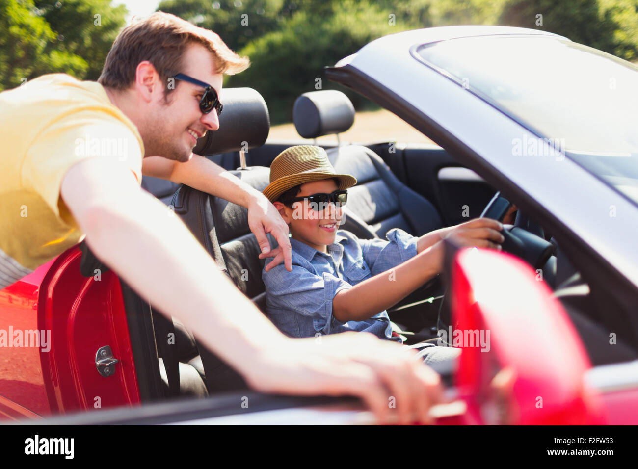 Father watching son pretend to drive in convertible - Stock Image