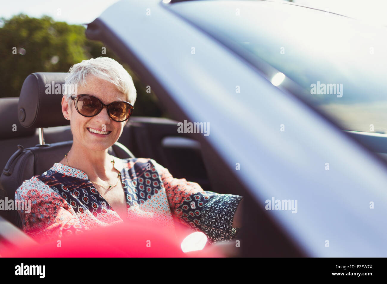 Portrait smiling senior woman in sunglasses driving convertible Stock Photo