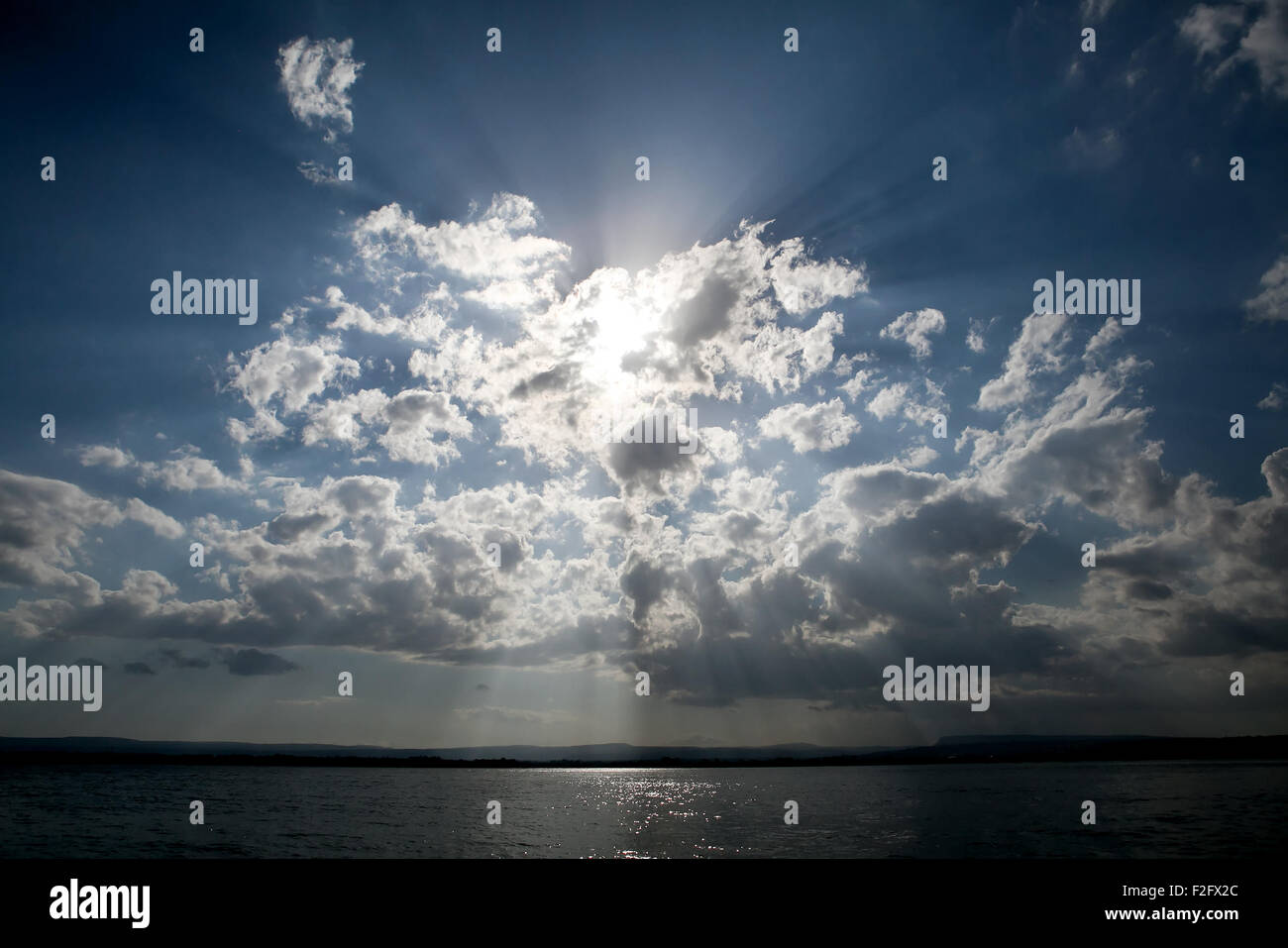 Blue sky with dramatic clouds and sun beams - Stock Image